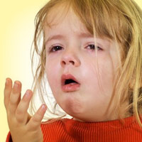 little girl coughing into her hand